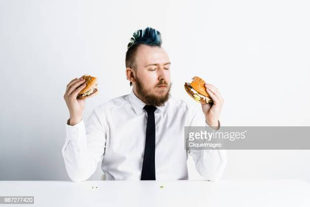 man choosing between burgers - cliqueimages ストックフォトと画像