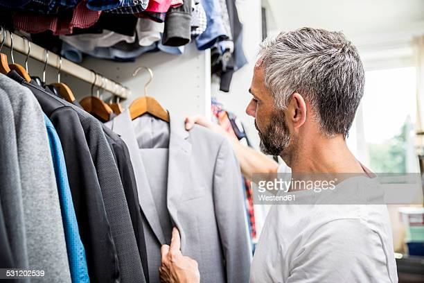 man choosing clothes at his walk-in closet - walk in closet stock photos and pictures