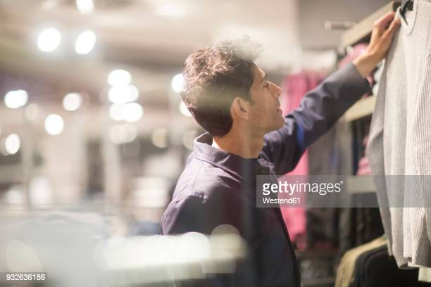 Man choosing clothes in shop