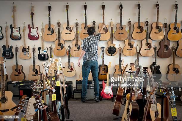 Man choosing guitar in shop