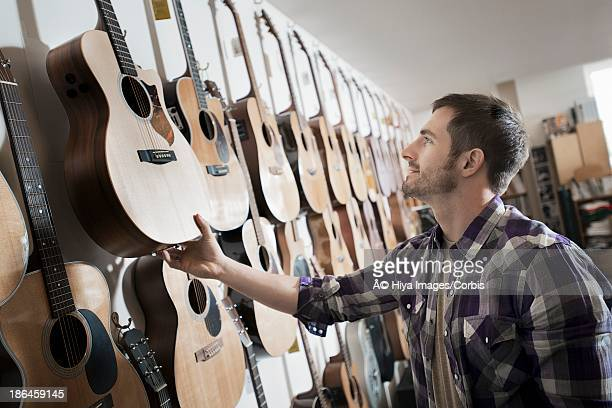 Man choosing guitar in shop