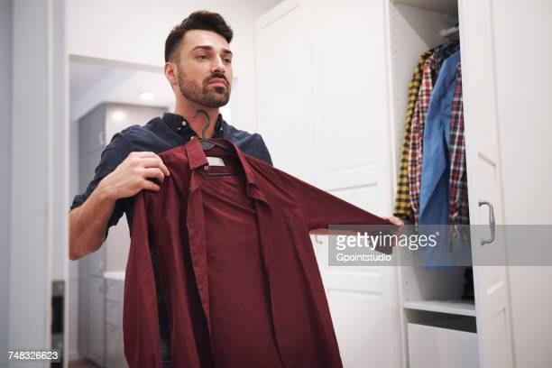 man choosing shirt from closet - escolher - fotografias e filmes do acervo