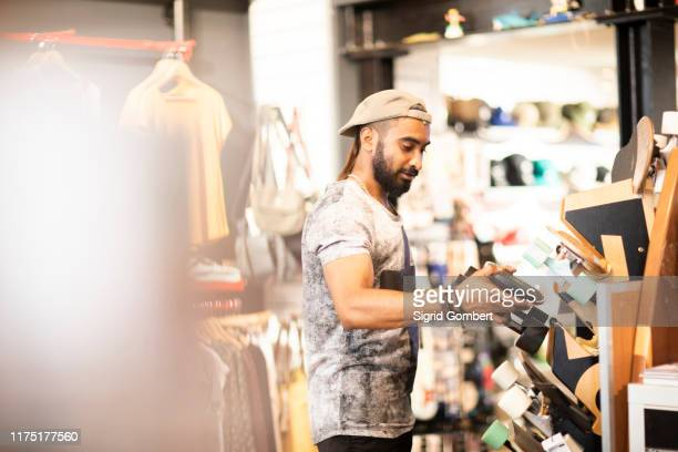 man choosing skateboard in shop - sports equipment stock pictures, royalty-free photos & images