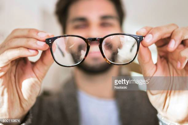 man choosing wearing glasses in optical store - occhiali da vista foto e immagini stock