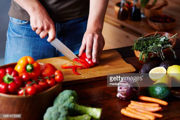man chopping bell pepper - red bell pepper stock pictures, royalty-free photos & images