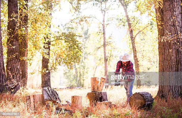 Man chopping firewood out in sunlit forest