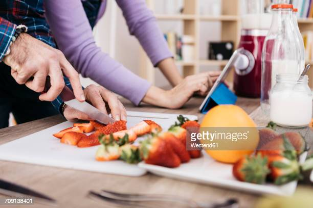 Man chopping strawberries while his girldfriend using tablet, partial view