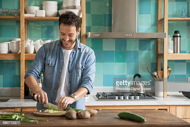 man chopping up fresh ingredients in kitchen - cortando preparando comida imagens e fotografias de stock