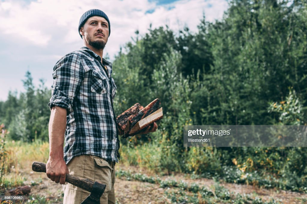 Man chopping wood in rural landscape : Stock-Foto
