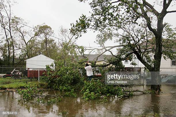 A man chops a tree that fell on his fence September 24 2005 Port Arthur Texas Hurricane Rita stormed ashore overnight damaging homes and businesses...
