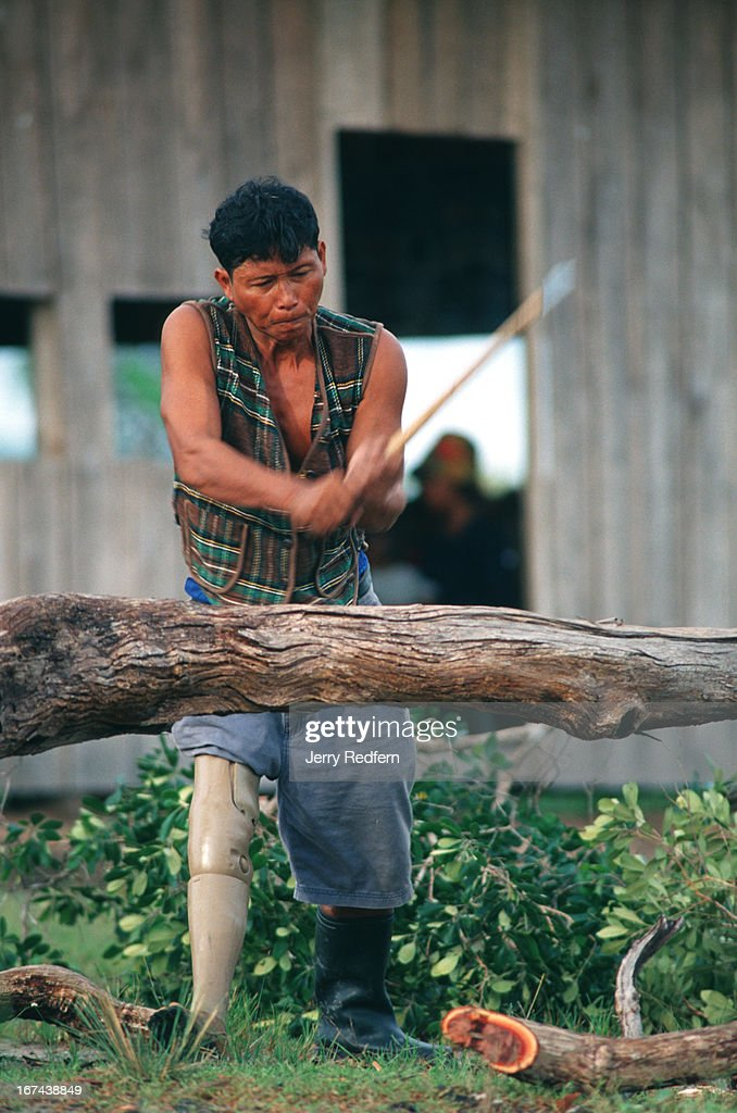 """A man chops a windfall tree in the main part of Veal Thom village. Deep in the hinterlands, down a rutted dirt road, a small village shelters the remnants of Cambodia's civil war. Some 200 disabled veterans - both Khmer Rouge and government soldiers - and their families have moved to Veal Thom, or """"Big Field."""" There they build huts, grow rice, cultivate flowers and do what society will not allow in their homelands: live in peace. Though they lost limbs and parts of their lives in Cambodia's civil war, their wounds mark them as outcasts in the Cambodian society.."""