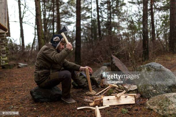 Man chops wood for campfire