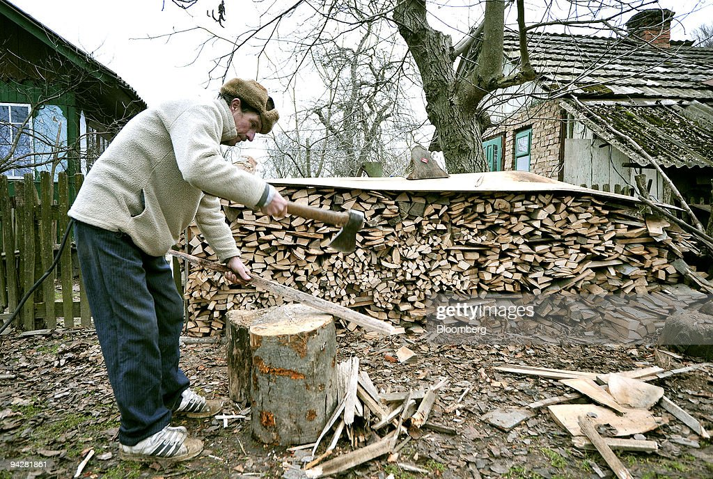 A man chops wood for fuel outside his house in Semyhyniv, Ukraine, on Saturday, Dec. 5, 2009. Ukraine expects the International Monetary Fund to release the next tranche of its bailout loan by the end of the year, Deputy Premier Hryhoriy Nemyria said. Photographer: John Guillemin/Bloomberg via Getty Images