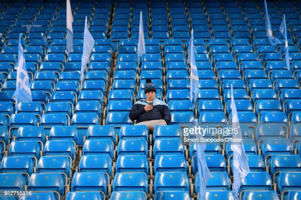 Man City fan sits alone before the Premier League match between Manchester City and West Bromwich Albion at the Etihad Stadium on January 31 2018 in...