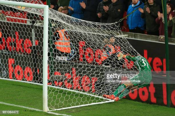 Man City goalkeeper Ederson ends up in the back of the goal net after scrambling to make a save during the Premier League match between Stoke City...