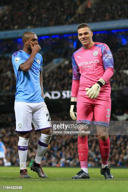 Man City goalkeeper Ederson smiles as Fernandinho of Man City talks to him during the Premier League match between Manchester City and Chelsea FC at...