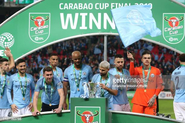 Man City goalkeeper Ederson waves a flag as he lines up on the winners podium with his teammates Sergio Aguero of Man City places the trophy on the...