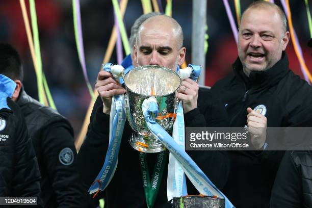 Man City manager Pep Guardiola kisses the trophy as he celebrates their victory during the Carabao Cup Final between Aston Villa and Manchester City...