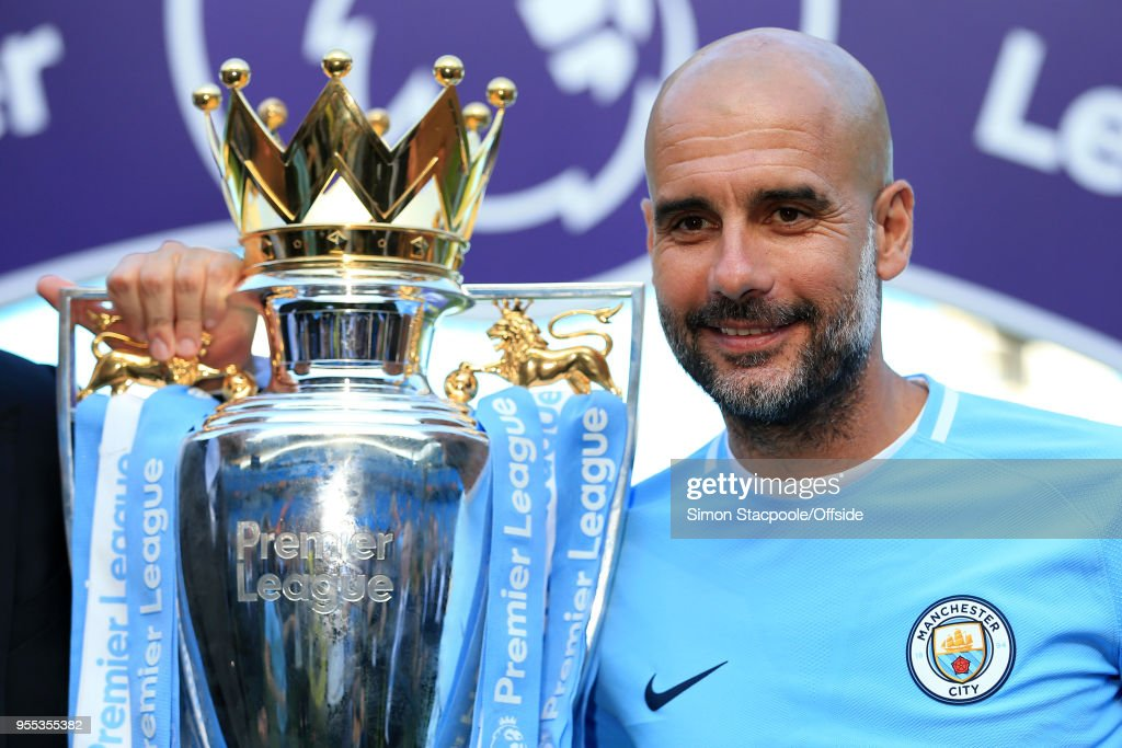 Man City manager Pep Guardiola poses with the trophy after the Premier League match between Manchester City and Huddersfield Town at the Etihad Stadium on May 6, 2018 in Manchester, England.