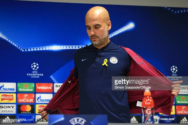 Man City manager Pep Guardiola removes his jacket to reveal a yellow ribbon on his shirt during a press conference prior to their UEFA Champions...