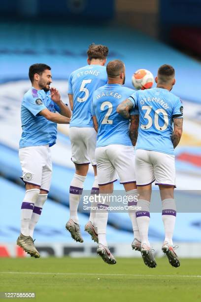 Man City players Ilkay Gundogan John Stones Kyle Walker and Nicolas Otamendi jump in the defensive wall during the Premier League match between...