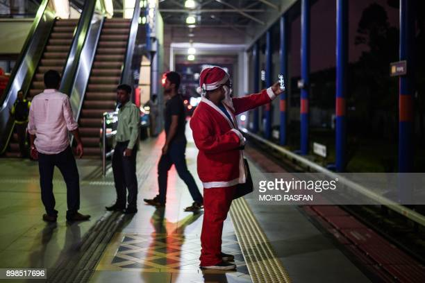 A man clad in a Santa Claus outfit takes selfies as he waits at a train station in Kuala Lumpur on December 25 2017 / AFP PHOTO / MOHD RASFAN