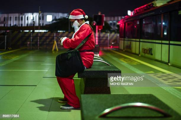 A man clad in a Santa Claus outfit waits at a train station in Kuala Lumpur on December 25 2017 / AFP PHOTO / MOHD RASFAN