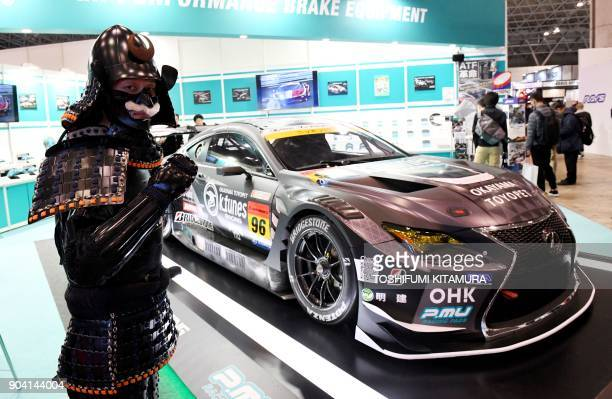 A man clad in Japanese traditional armour poses beside a Lexus LC500 GT3 race car at the ProjectMu booth of the Tokyo Auto Salon at the Makuhari...