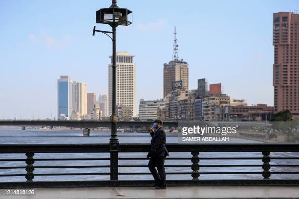Man clad in mask due to the COVID-19 coronavirus pandemic walks along the Kasr el-Nil bridge connecting the island district of Zamalek to the city...