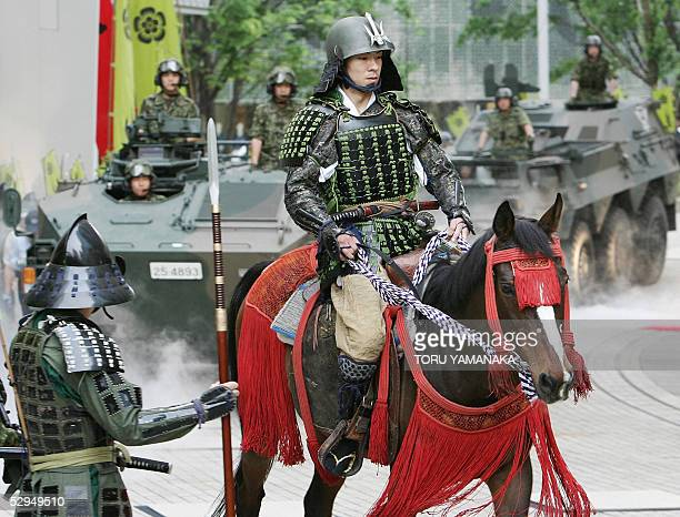 A man clad in samurai armour rides horseback to lead armored personnel carriers of the Japan's Ground SelfDefense Force during a promotion event for...