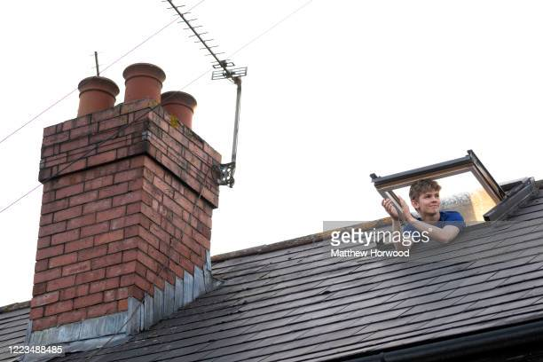 """Man claps from a skylight of a house on Sudcroft Street on May 07, 2020 in Cardiff, United Kingdom. Following the success of the """"Clap for Our..."""