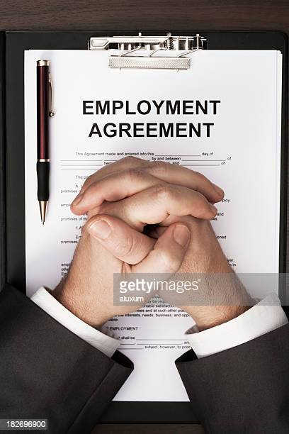 Man clasped hands over employment agreement document