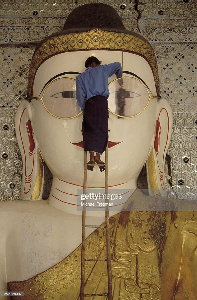 Man Cleaning a Spectacles Buddha Statue : Stock Photo
