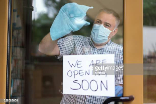 man cleaning and disinfecting the store before reopening - reopening stock pictures, royalty-free photos & images
