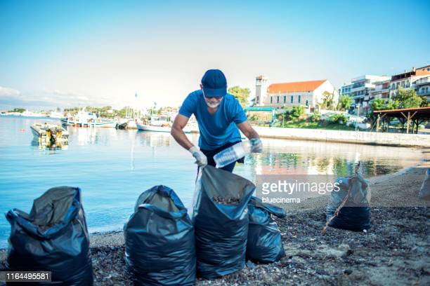 man cleaning beach - one man only stock pictures, royalty-free photos & images