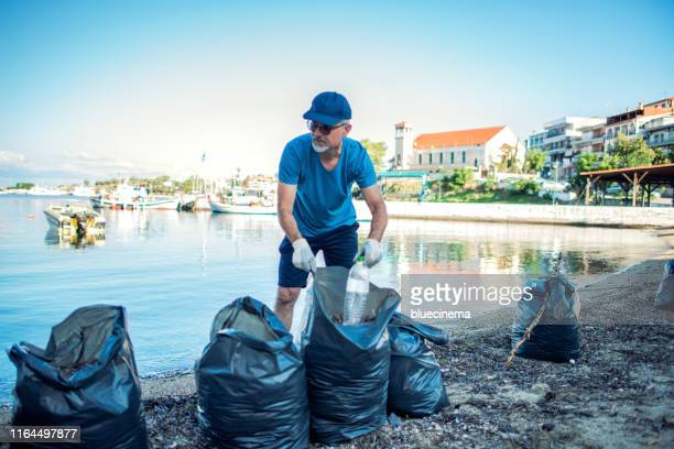 man cleaning beach - selfless stock pictures, royalty-free photos & images