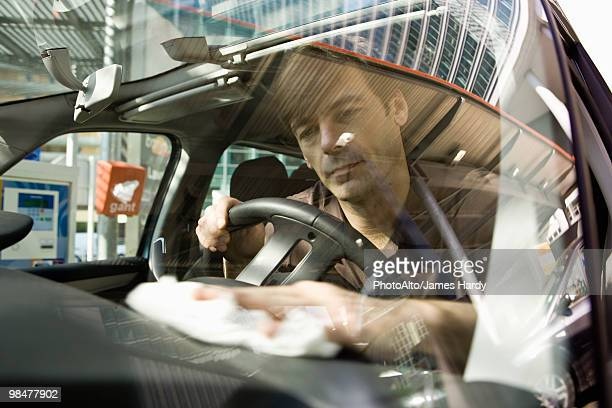 Man cleaning car dashboard
