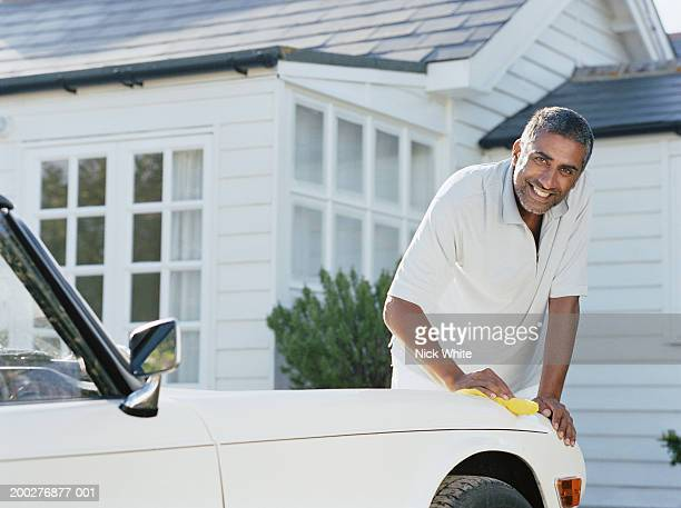 Man cleaning car parked outside house, smiling, portrait