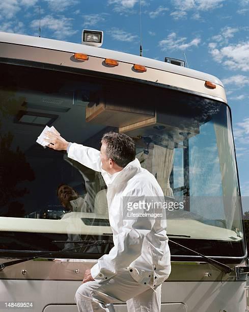 Homme nettoyage autocar pare-brise, vue latérale