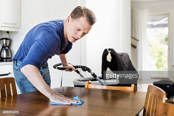 Man cleaning dining table while holding baby carriage in kitchen