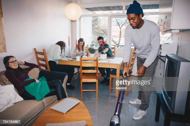 Man cleaning floor while friends sitting in college dorm room