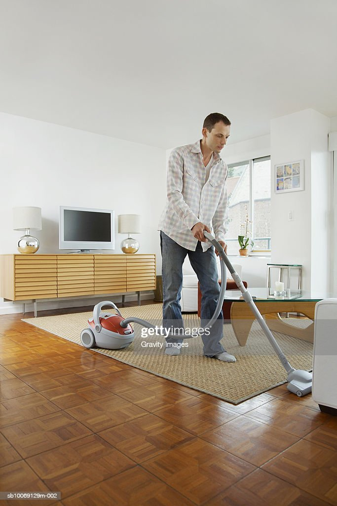 Man cleaning floor with vacuum cleaner : Bildbanksbilder