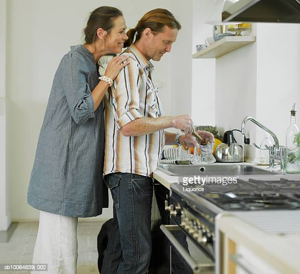 man cleaning glasses, woman watching from behind, side view - role reversal stock photos and pictures