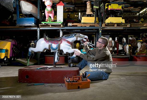 Man cleaning horse in workshop, side view