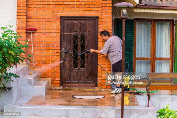 man cleaning house with water spray - high pressure cleaning stock pictures, royalty-free photos & images