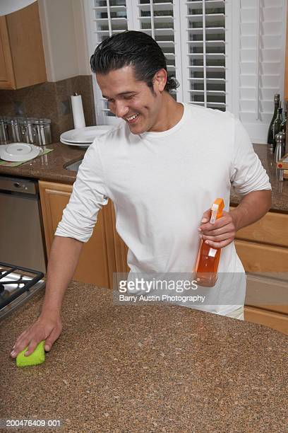 Man cleaning kitchen counter, smiling