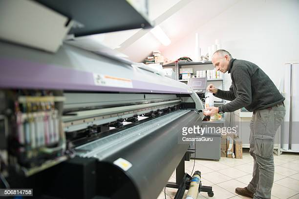 Man Cleaning Large Format Printer Head