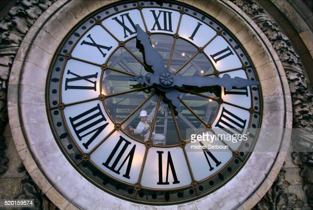 man cleaning musee d'orsay clock - musee d'orsay stock pictures, royalty-free photos & images