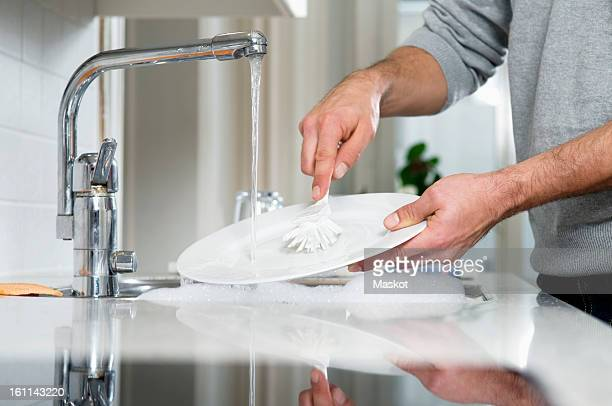 man cleaning plate - crockery stock pictures, royalty-free photos & images