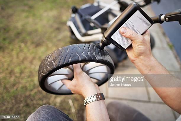 Man cleaning pram wheel